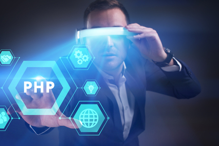 Business, Technology, Internet and network concept. Young businessman working in virtual reality glasses sees the inscription: PHP Stock Photo