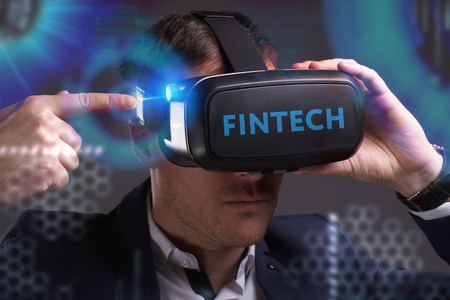 Business, Technology, Internet and network concept. Young businessman working in virtual reality glasses sees the inscription: Fintech