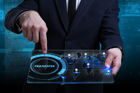 Business, Technology, Internet and network concept. Young businessman working on a virtual screen of the future and sees the inscription: Franchise Stock Photo