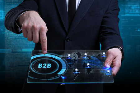 Business, Technology, Internet and network concept. Young businessman working on a virtual screen of the future and sees the inscription: B2B
