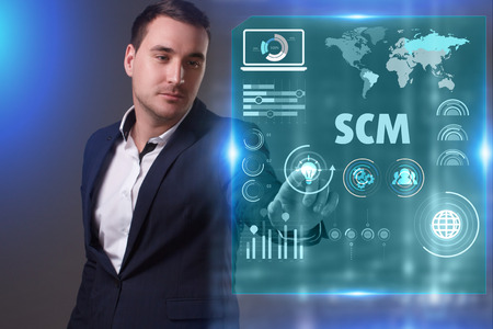 Business, Technology, Internet and network concept. Young businessman working on a virtual screen of the future and sees the inscription: SCM