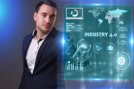 Business, Technology, Internet and network concept. Young businessman working on a virtual screen of the future and sees the inscription: Industry 4.0