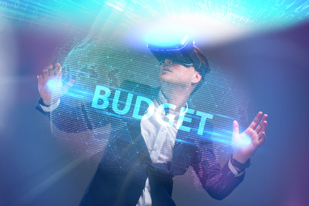 Business, Technology, Internet and network concept. Young businessman working in virtual reality glasses sees the inscription: Budget