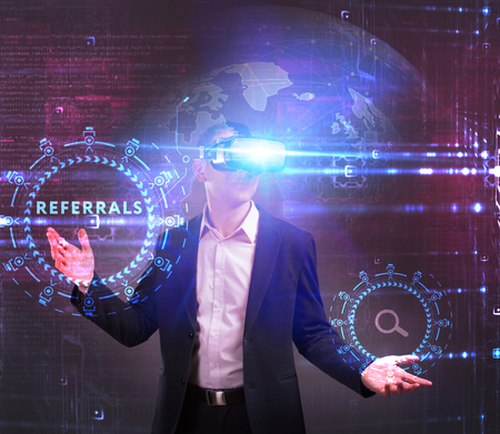 Business, Technology, Internet and network concept. Young businessman working in virtual reality glasses sees the inscription: Referrals Stock Photo