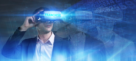 Business, Technology, Internet and network concept. Young businessman working in virtual reality glasses sees the inscription: Franchise Stock Photo
