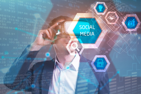 Business, Technology, Internet and network concept. Young businessman working in virtual reality glasses sees the inscription: Social media Stock Photo
