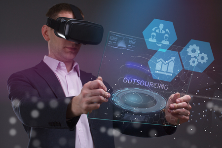 The concept of business, technology, the Internet and the network. A young entrepreneur working on a virtual screen of the future and sees the inscription: Outsourcing