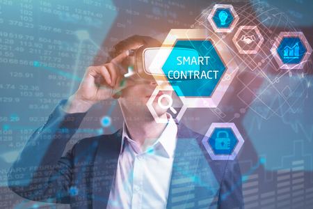 Business, Technology, Internet and network concept. Young businessman working in virtual reality glasses sees the inscription: smart contract Stock Photo