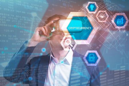 Business, Technology, Internet and network concept. Young businessman working in virtual reality glasses sees the inscription: Cryptocurrency