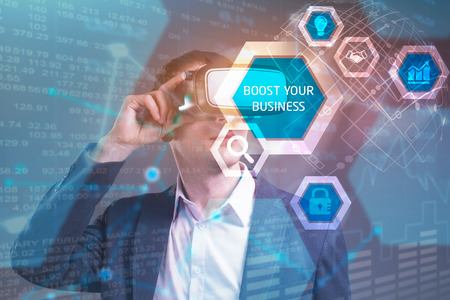 Business, Technology, Internet and network concept. Young businessman working in virtual reality glasses sees the inscription: Boost your business Stock Photo