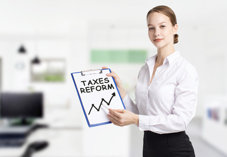 Business, technology, internet and networking concept. Young entrepreneur showing keyword: taxes reform