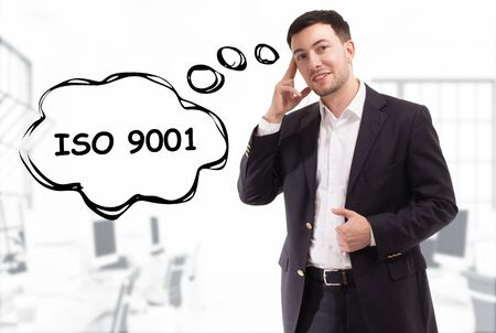 Business, technology, internet and network concept. The young businessman comes up with the keyword: ISO 9001