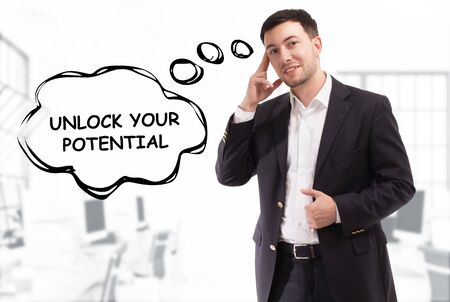 Business, technology, internet and network concept. The young businessman comes up with the keyword: Unlock your potential