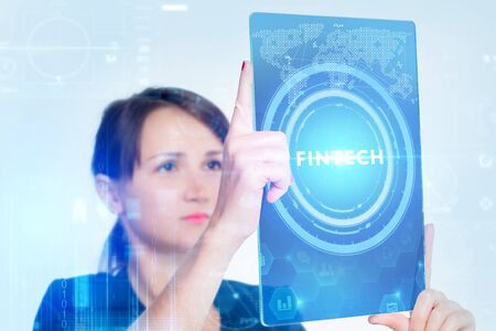 The concept of business, technology, the Internet and the network. A young entrepreneur working on a virtual screen of the future and sees the inscription: fintech 写真素材