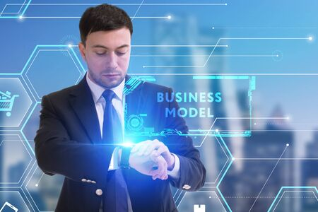 The concept of business, technology, the Internet and the network. A young entrepreneur working on a virtual screen of the future and sees the inscription: Business model Zdjęcie Seryjne