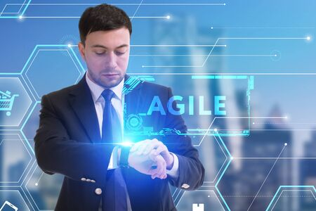 The concept of business, technology, the Internet and the network. A young entrepreneur working on a virtual screen of the future and sees the inscription: Agile