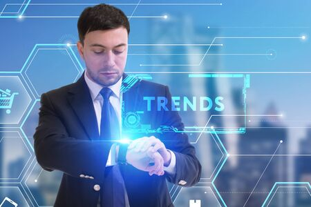 The concept of business, technology, the Internet and the network. A young entrepreneur working on a virtual screen of the future and sees the inscription: Trends