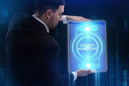 The concept of business, technology, the Internet and the network. A young entrepreneur working on a virtual screen of the future and sees the inscription: Content marketing