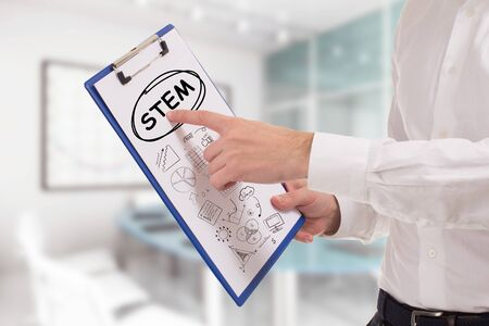 Business, technology, internet and network concept. Young businessman points to the keyword: STEM
