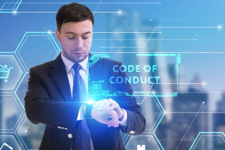 The concept of business, technology, the Internet and the network. A young entrepreneur working on a virtual screen of the future and sees the inscription: Code of conduct Zdjęcie Seryjne