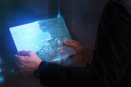 Concept d'affaires, de technologie, d'Internet et de réseau. Jeune homme d'affaires travaillant sur un écran virtuel du futur et voit l'inscription: Gouvernance