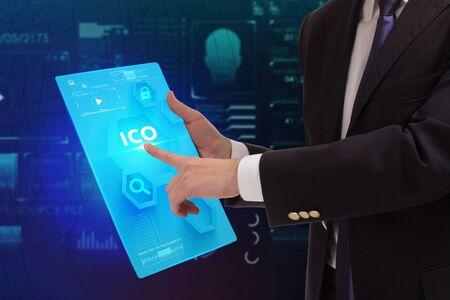 Business, Technology, Internet and network concept. Young businessman working on a virtual screen of the future and sees the inscription: ICO