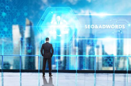 Business, Technology, Internet and network concept. Young businessman working on a virtual screen of the future and sees the inscription: SEO&AdWords
