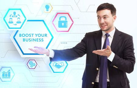 Business, Technology, Internet and network concept. Young businessman working on a virtual screen of the future and sees the inscription: Boost your business Zdjęcie Seryjne