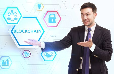 Business, Technology, Internet and network concept. Young businessman working on a virtual screen of the future and sees the inscription: Blockchain Zdjęcie Seryjne
