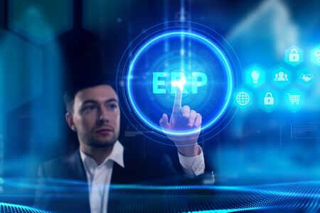 Business, Technology, Internet and network concept. Young businessman working on a virtual screen of the future and sees the inscription: ERP Stock Photo