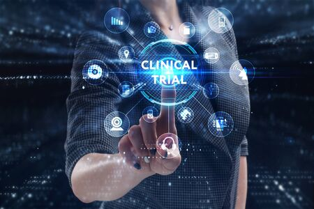 Business, Technology, Internet and network concept. Young businessman working on a virtual screen of the future and sees the inscription: Clinical trial Фото со стока