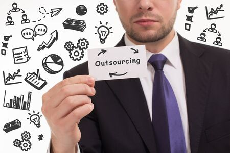 Business, technology, internet and network concept. Young businessman thinks over the steps for successful growth: Outsourcing 스톡 콘텐츠