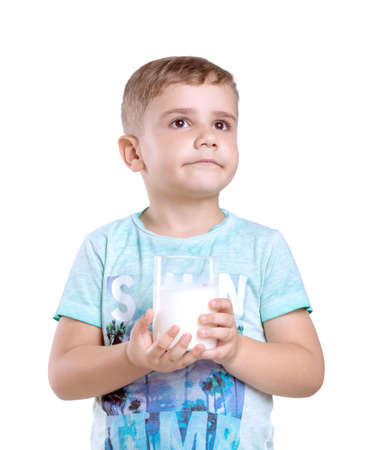 Close-up portrait of a nice little boy with a glass of organic milk isolated on a white background. Beautiful little boy with a glass of milk wondering about its amazing taste.