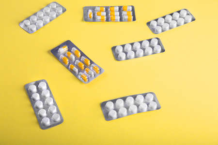 doze: Close-up of medication on a bright yellow background. Tablets in blisters: painkillers, antibiotics, vitamins, drugs, aspirin and other.  Pharmaceutical medicament, care in container for health.