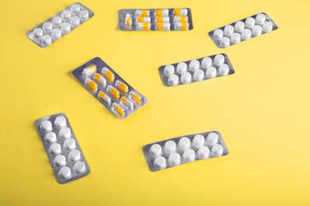pilule: Primer plano de la medicación en un fondo amarillo brillante. Comprimidos en ampollas: analgésicos, antibióticos, vitaminas, medicamentos, aspirina y otros. Medicamento farmacéutico, cuidado en el envase para la salud. Foto de archivo