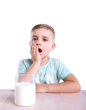 A huge glass full of flavoursome healthful milk is standing on a bright massive wooden table next to the surprised cute little blond boy wearing a blue T-shirt.