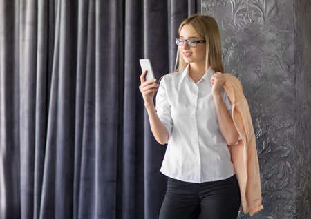 A beautiful successful young businesswoman in a white blouse and fashionable glasses is holding a phone and smiling in the office. A cheerful professional business woman is holding a coat.