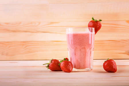 A glass of fresh, tasty, sweet and beautiful smoothies on a light brown wooden table. One strawberry is on top on a glass cup. A few strawberries are near a full jar of strawberry drink. Stok Fotoğraf