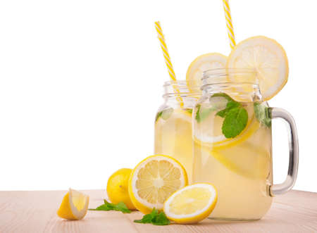 Healthy organic lemonade cocktails in two pretty huge and transparent glasses and with cute yellow straws and ripe lemons, water and fresh leaves of bright green mint isolated on a white background. Stock Photo