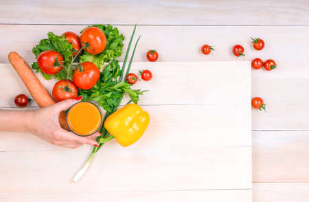 healthful: Close-up hand holding a glass full of juice. Organic food ingredients on a wooden background. Nutritious tomatoes. Healthful vegetables: pepper and carrot. Delicious greens.