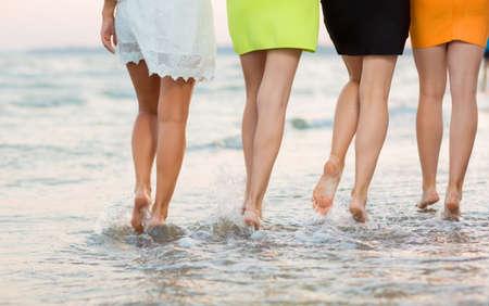 Schattige meisjes met lange benen lopen in de buurt van de zee in het zand. Lange en soepele vrouwelijke benen op de achtergrond van de zee, uitzicht vanaf de achterkant. Close-up van de benen van een leuke sportenvrouw. Mooie meisjes op een tropisch strand zee.