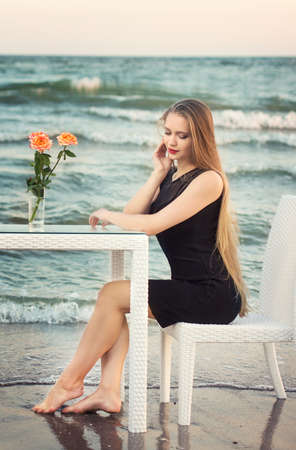 An attractive young woman with long blonde hair and in a pretty and black dress is sitting at a table in the background of the sea. Beautiful young girl on the background of the sea.