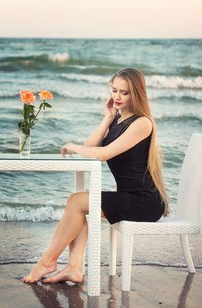 Een aantrekkelijke jonge vrouw met lang blond haar en in een mooie en zwarte jurk zit aan een tafel op de achtergrond van de zee. Mooi jong meisje op de achtergrond van de zee.