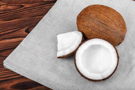 healthful: Close-up tasteful coconuts on a dark wooden background. Healthful coconut on a bright gray piece of cloth. Delicious natural ingredients. Exotic tropical nuts. Stock Photo
