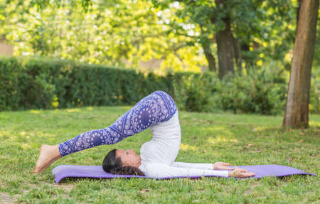 A concentrated lady on a natural background. Young active woman practicing sports. Balanced beautiful sports girl in a park. Fitness lifestyle. A girl working out on a purple mat.