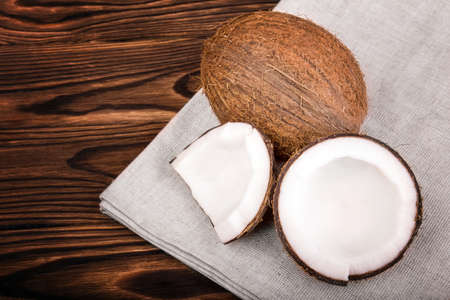 healthful: Tasteful tropical nuts on a gray piece of cloth on a dark wooden background. Nutritious cracked coconuts on a brown table. Healthful organic summer fruits.
