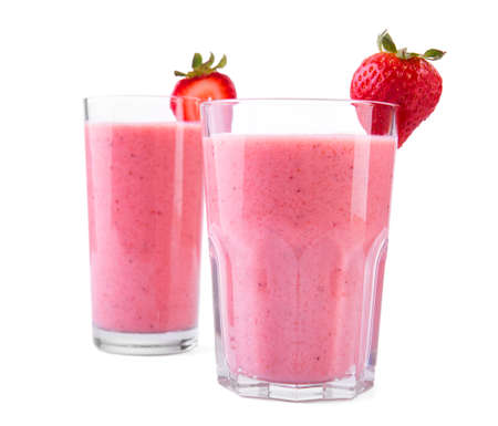 Summer dessert or breakfast - a strawberry milkshake with berries and milk, in a small jar, solated on a white background. Strawberry yogurt with fresh berries and organic milk. Refreshing milkshkes.