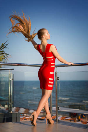An extremely attractive young female posing on a sunny balcony on a bright blue background. A stunning lady in a saturated red dress with holes. A tall girl with a beautiful long dark blonde hair. Stock Photo