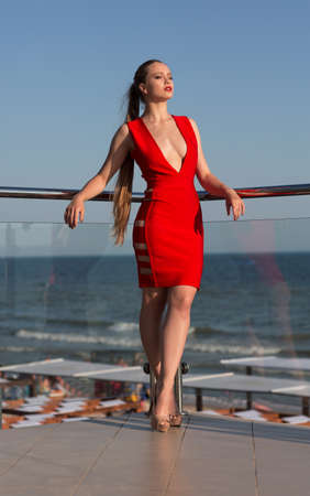 水色の海の背景に明るいテラスの上に立って高いヒールでスタイリッシュで幻想的な女性。深い谷間と美しい赤いドレスで熱い女の子。ポニーテー