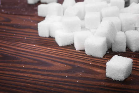 Many cubes of sweet sugar on a dark brown wooden table. White organic, refined sugar and sweet food ingredient on the table. Unhealthy ingredients and products. Unhealthy diet concept.